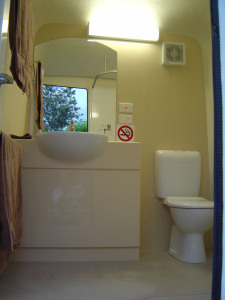 Photo of vanity, toilet and mirror.
